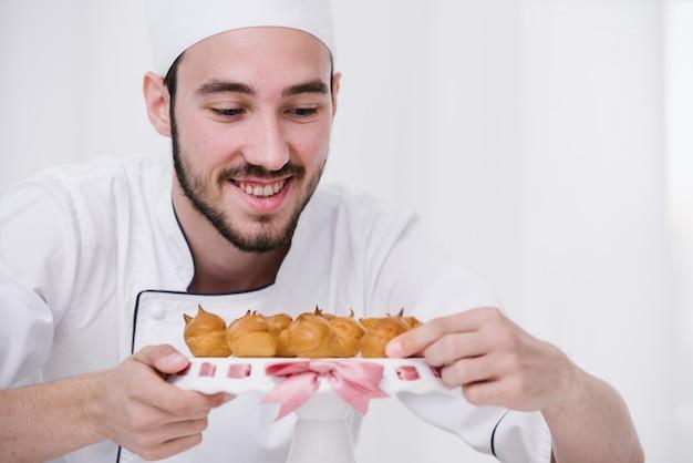 Smiley szef kuchni przedstawia płomienną bezę na talerzu Darmowe Zdjęcia