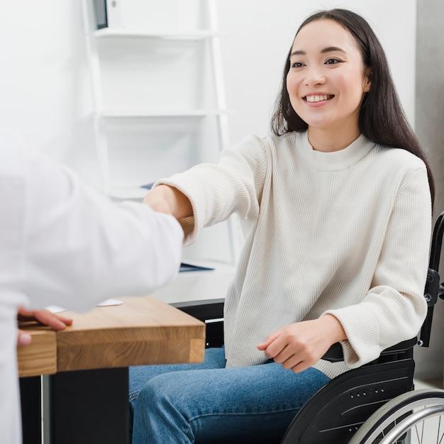 Smiling portret niepełnosprawnej młodej kobiety siedzącej na wózku inwalidzkim, ściskając ręce z osobą w miejscu pracy Darmowe Zdjęcia
