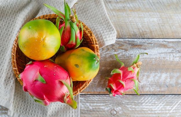 Smoczy Owoc W Wiklinowym Koszu Leżał Płasko Na Drewnianym Ręczniku Kuchennym Darmowe Zdjęcia