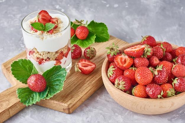 Smoothie z lato truskawką w szklanym słoju i świeżych jagodach w drewnianym pucharze na szarym tle Premium Zdjęcia