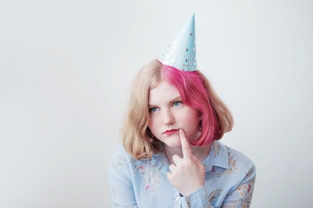 Smutna Dziewczyna Nastolatka W Urodzinowym Kapeluszu Premium Zdjęcia