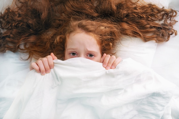 Smutna dziewczynka przestraszony śpi i ciągnąc kołdrę na głowie. Premium Zdjęcia