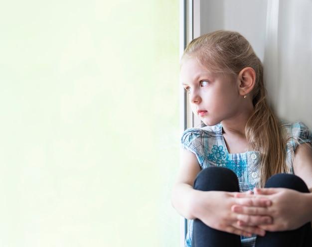 Smutna Dziewczynka Przy Oknie Premium Zdjęcia