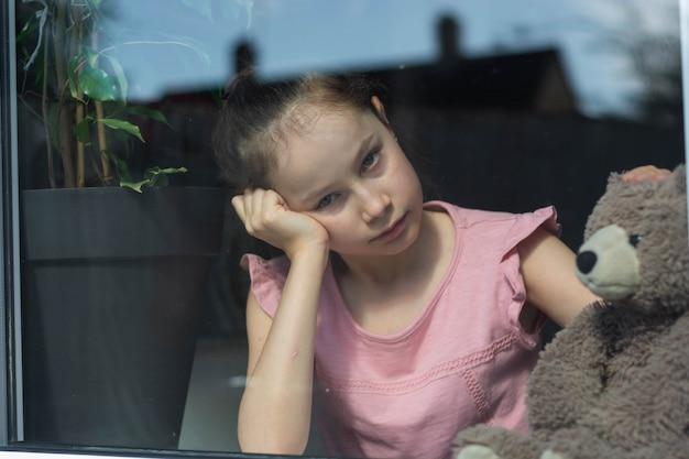 Smutna Dziewczynka Z Misiem W Oknie. Premium Zdjęcia