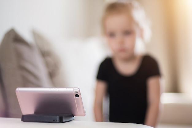 Smutna I Zmęczona Dziewczynka Studiuje W Domu Przed Smartfonem. Kształcenie Na Odległość, Edukacja Online Dla Dzieci. Uzależnienie Od Komputera Dziecka, Kontrola Rodzicielska. Premium Zdjęcia