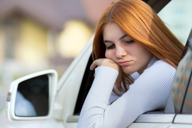Smutna Kobieta Kierowca Patrząc Przez Okno Samochodu. Premium Zdjęcia