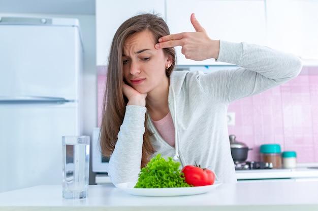 Smutna, Nieszczęśliwa Kobieta Jest Zmęczona Dietą, Eksterminuje Się Dietą I Zmusza Do Jedzenia Organicznych, Czystych, Zdrowych Potraw Premium Zdjęcia