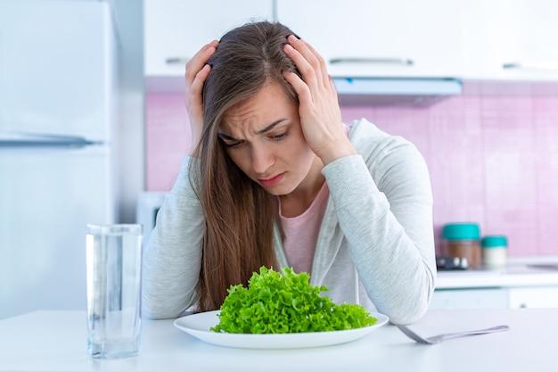 Smutna, Nieszczęśliwa Kobieta Jest Zmęczona Dietą I Nie Chce Jeść Ekologicznych, Zdrowych I Zdrowych Posiłków Premium Zdjęcia
