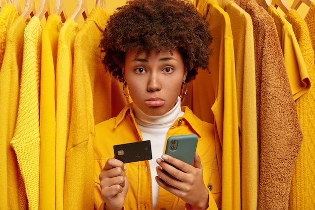 Smutna Sfrustrowana Afro Kobieta Dokonuje Płatności Przez Portfel Internetowy, Trzyma Kartę Kredytową I Nowoczesny Telefon Komórkowy Darmowe Zdjęcia