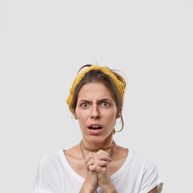 Smutna Zmartwiona Zdziwiona Kobieta Pozuje W Geście Modlitwy, Prosi O Przeprosiny, Ma Niezadowolony Wyraz Twarzy Darmowe Zdjęcia