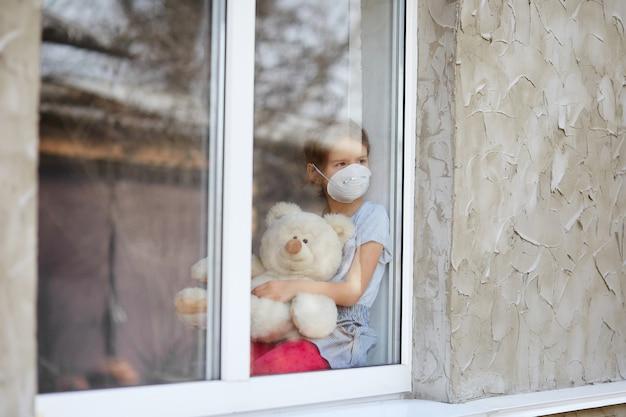 Smutne Dziecko, Mała Dziewczynka W Masce Z Misiem Patrzącym Z Okna, Kwarantanna Koronawirusa Premium Zdjęcia