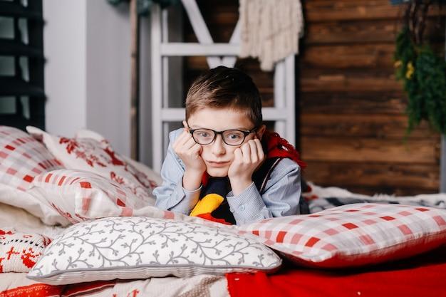 Smutny chłopiec w okularach leży na łóżku Premium Zdjęcia
