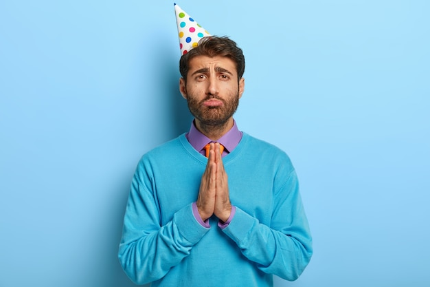 Smutny Facet Z Kapeluszem Urodzinowym, Pozowanie W Niebieskim Swetrze Darmowe Zdjęcia