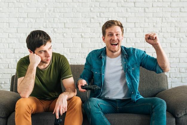Smutny mężczyzna patrzeje szczęśliwego przyjaciela rozwesela po wygrywać grę wideo Darmowe Zdjęcia