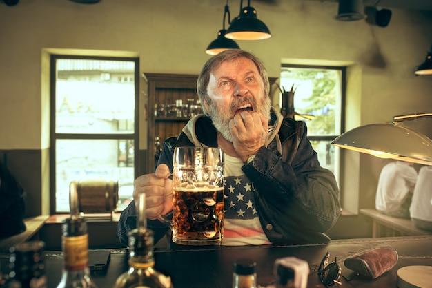 Smutny Starszy Mężczyzna Pije Alkohol W Pubie I Ogląda Program Sportowy W Telewizji Darmowe Zdjęcia