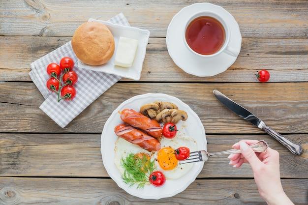 Śniadanie Angielskie Z Jajkiem Sadzonym, Kiełbasą, Grzybami, Grillowanymi Pomidorami I Filiżanką Herbaty Na Rustykalnym Drewnianym Stole. Widok Z Góry Premium Zdjęcia