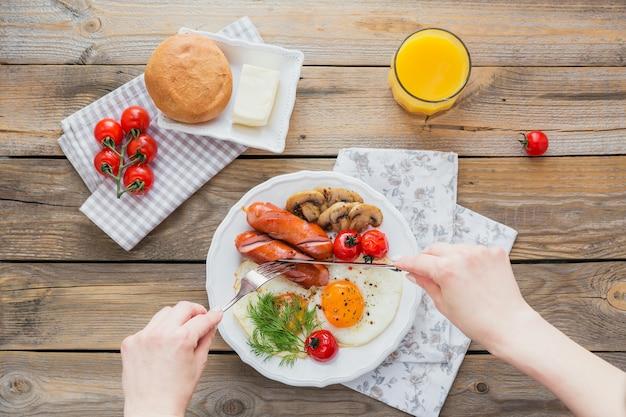 Śniadanie Angielskie Z Jajkiem Sadzonym, Kiełbasą, Grzybami, Grillowanymi Pomidorami I świeżym Sokiem Pomarańczowym Na Rustykalnym Drewnianym Stole. Widok Z Góry Premium Zdjęcia