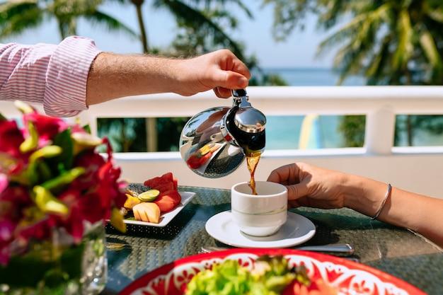 Śniadanie młodej pary w tropikalnym kurorcie z bliska. mężczyzna nalewa herbatę kobiecie. stół to talerz z owocami tropikalnymi. letnie wakacje w gorących krajach Premium Zdjęcia
