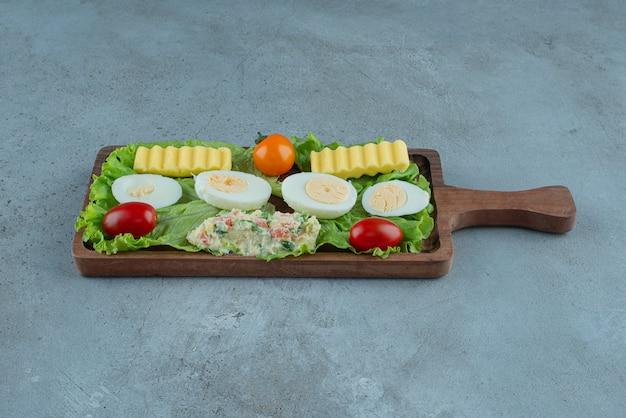 Śniadanie Na Drewnianej Tacy Z Warzywami, Jajkiem Na Twardo, Masłem I Porcją Sałatki Na Marmurowym Tle. Wysokiej Jakości Zdjęcie Darmowe Zdjęcia
