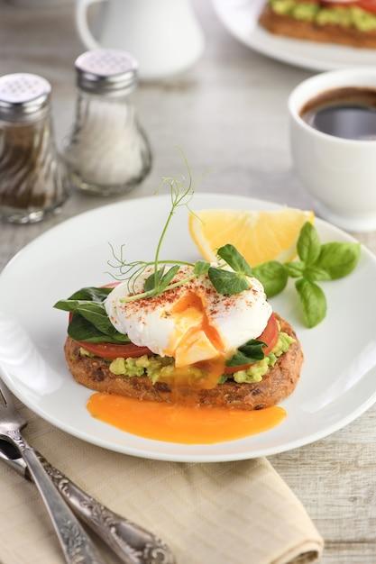 Śniadanie. Najlepsze Jajka Po Benedyktyńsku Na Kromce Tostowego Chleba Zbożowego Z Guacamole I Szpinakiem Premium Zdjęcia