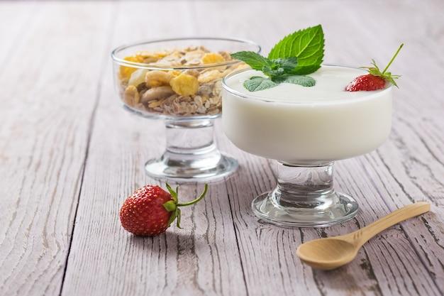 Śniadanie Z Jogurtem I Płatkami Owsianymi Na Drewnianym Stole Premium Zdjęcia