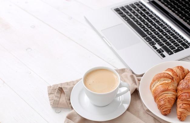 Śniadanie Z Rogalikami I Kawą W Pobliżu Laptopa Darmowe Zdjęcia