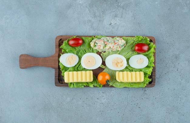 Śniadanie Z Warzywami, Jajkiem Na Twardo, Masłem I Porcją Sałatki Na Marmurowym Tle. Wysokiej Jakości Zdjęcie Darmowe Zdjęcia