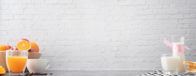 Śniadaniowy Stół Z świeżo Sokiem Pomarańczowym, Szkła Mlekiem I Filiżanką Kawy Na Białym ściana Z Cegieł Tekstury Tle. Szeroki Stół. Premium Zdjęcia