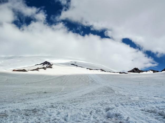 Śnieżna Górska Dolina, Pokryta Szarymi Chmurami. Ledwo Zauważalne Sylwetki Ludzi Idących Przez Dolinę. Premium Zdjęcia