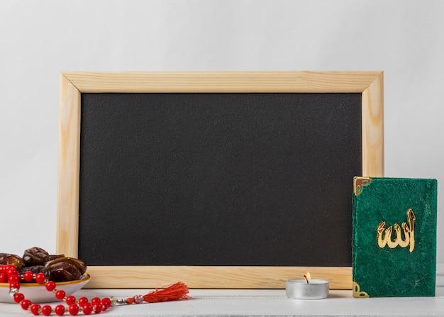 Soczyste daty; czerwone paciorki różańca; świeca i święta kuran książka przed czarną tablicą na białym tle Darmowe Zdjęcia
