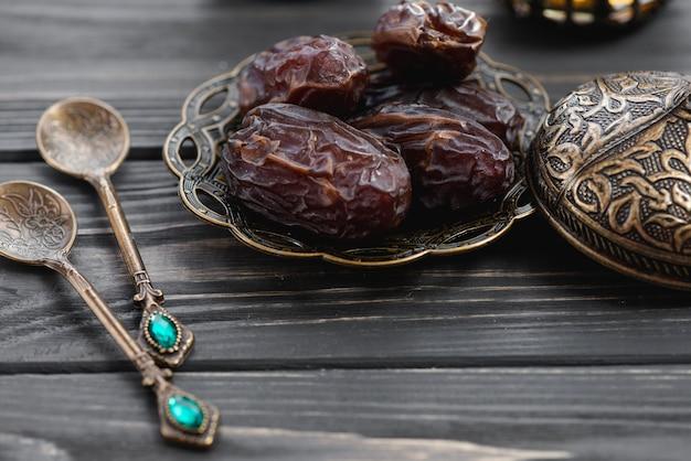 Soczyste daty na metalowe płytki z tureckimi wzorami i ozdoby łyżki na stole Darmowe Zdjęcia