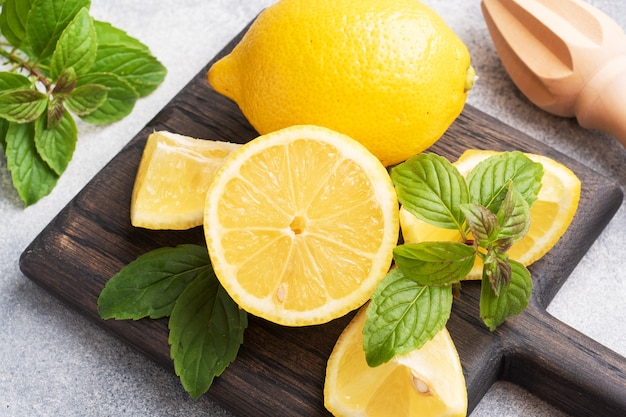 Soczyste żółte Cytryny W Całości, Pokrojone W świeże Liście Mięty Premium Zdjęcia
