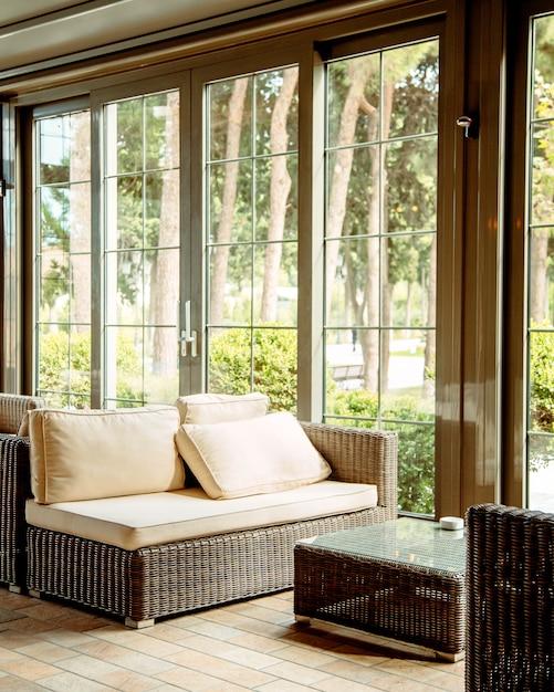 Sofa Zewnętrzna Z Beżowymi Poduszkami I Stolikiem Kawowym Przed Oknem Restauracji Darmowe Zdjęcia