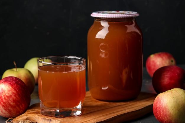 Sok Jabłkowy W Szklance I Słoiku, Gotowany W Sokowirówce, Zbierając Sok Z Uprawy Jabłek Na Ciemnym Tle Premium Zdjęcia