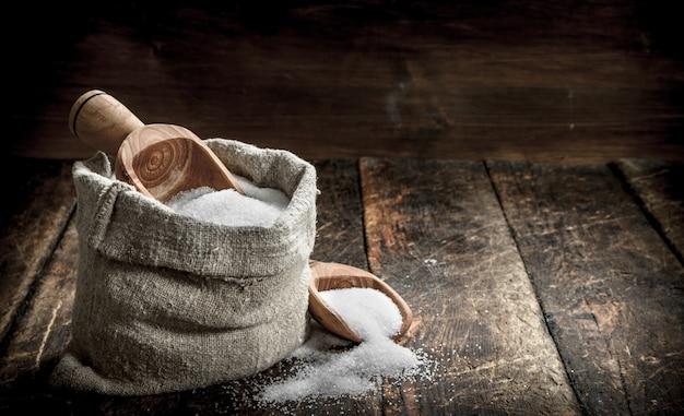Sól W Drewnianej łyżce. Na Drewnianym Tle. Premium Zdjęcia