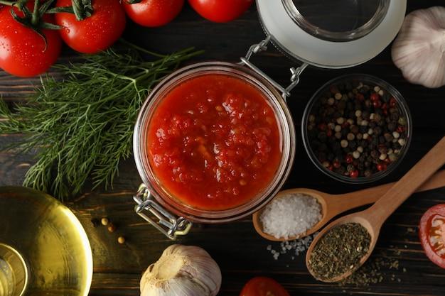 Sos Chili, Czosnek, Pomidory Czereśniowe, Oliwa Z Oliwek, Przyprawy Na Drewniane Tła, Z Bliska. Widok Z Góry Premium Zdjęcia
