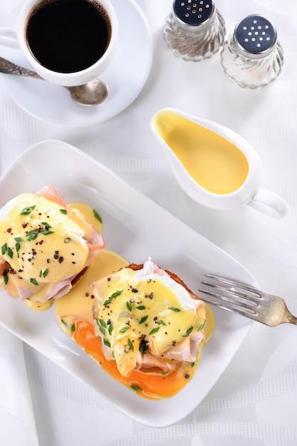 Sos Maślany Holenderski W Sosie Własnym Na śniadanie Podawany Z Eggs Benedict - Smażoną Angielską Bułką, Szynką, Jajkami W Koszulce, Filiżanką Kawy Premium Zdjęcia