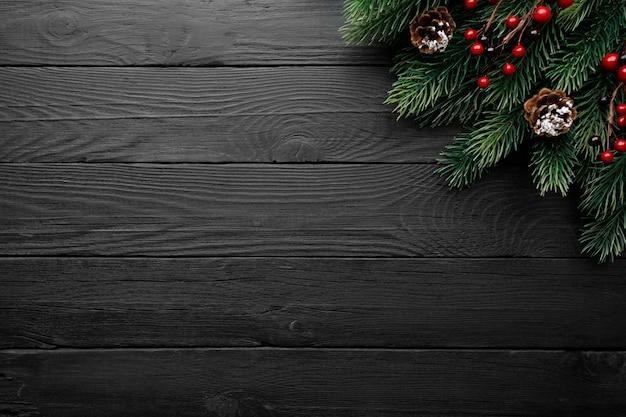 Sosna Gałąź Z Czerwonymi Jagodami I Szyszkami Na Czarnym Drewnianym Stole Premium Zdjęcia