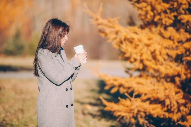 Spadku pojęcie - piękna kobieta pije kawę w jesień parku pod spadku ulistnieniem Premium Zdjęcia