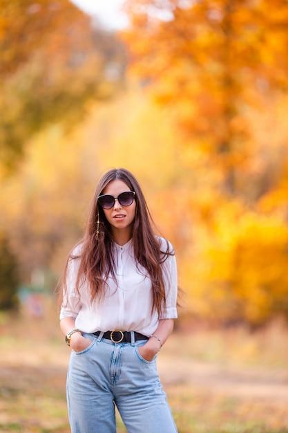 Spadku pojęcie - piękna kobieta w jesień parku pod spadku ulistnieniem Premium Zdjęcia