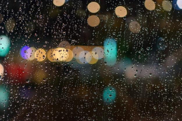 Spadł Deszcz Na Okno. Podczas Gdy Przez Okno Przechodzi światło Jako Bokeh. Premium Zdjęcia
