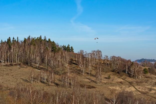 Spadochroniarz na niebie nad drzewami rosnącymi na zboczu góry wczesną wiosną Premium Zdjęcia