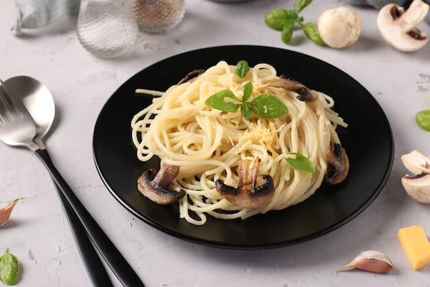 Spaghetti Z Pieczarkami I Bazylią Na Czarnym Talerzu Na Szarym Tle Premium Zdjęcia
