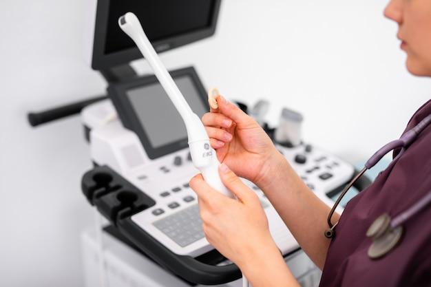 Specjalny Czujnik Ultradźwiękowy Nowoczesnego Skanera Ultradźwiękowego Do Kontroli Dopochwowej I Małej Prezerwatywy Medycznej W Rękach Lekarza Młodej Kobiety Przygotowującej Się Do Skanu Urządzenia. Premium Zdjęcia