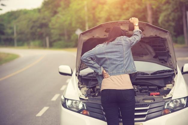 Spection kobiet otworzyła kaptur zepsuty samochód z boku zobacz silniki, które są uszkodzone lub Premium Zdjęcia