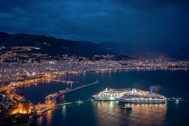 Spektakularna Noc Na Wybrzeżu Morskim Ze światłami Miasta I Statku Wycieczkowego Odbijanymi W Wodzie Darmowe Zdjęcia