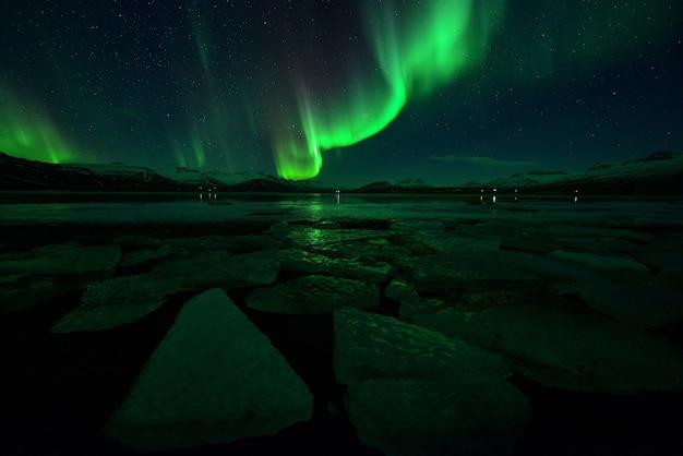 Spektakularny Pokaz Zorzy Polarnej W Nocy Nad Górami, Spektakularna Zorza Polarna I Nocna Gwiazda Na Islandii Premium Zdjęcia