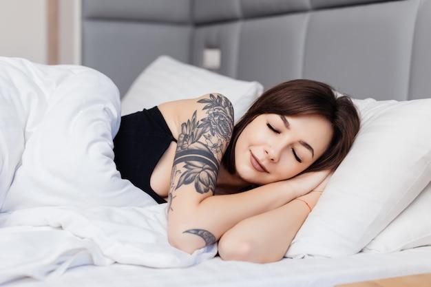 Śpiąca Brunetka Leży Na łóżku Rano Obudzić Się, Rozciągając Ramiona I Ciało Darmowe Zdjęcia