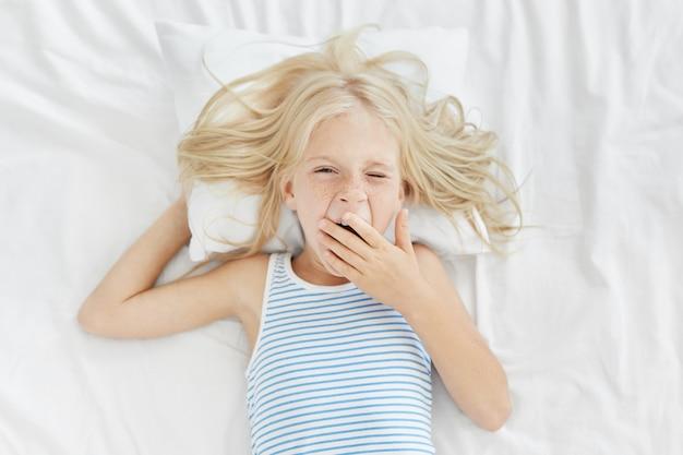 Śpiąca Dziewczyna Budzi Się Wcześnie Rano, Zasłaniając Usta Dłonią Podczas Ziewania, Chodzenia Do Szkoły Lub Przedszkola. Blondynki Urocze Dziecko W Marynarskiej Koszulce Leżące Na Białej Pościeli, Właśnie Się Budzi Darmowe Zdjęcia