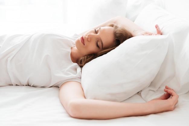 Śpiąca Młoda Kobieta Leży W łóżku Z Zamkniętymi Oczami. Darmowe Zdjęcia